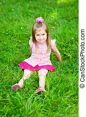 Cute little girl sitting on grass