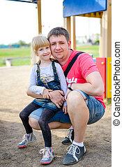 Cute little girl sitting on knee of father
