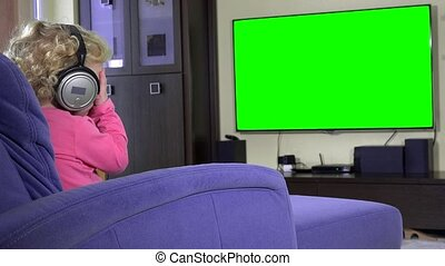 cute little girl sitting on sofa with headphones and watching tv at home