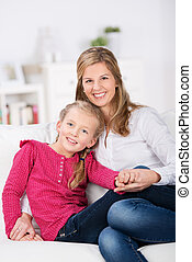 cute little girl sitting on sofa with her mother
