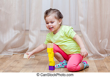 Cute little girl sitting on the floor and playing with building