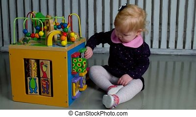 Cute little girl sitting on the floor and playing