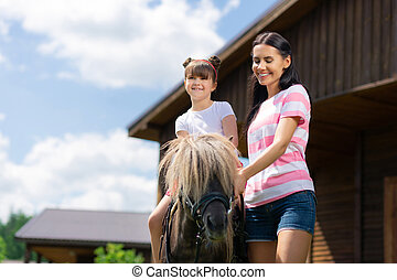 Cute little girl sitting on the horse posing with her mom