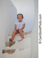 Cute little girl sitting on the steps of old house in...