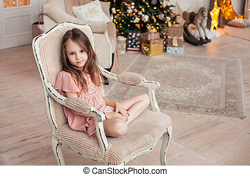 Cute little girl sitting on vintage armchair against cozy interior with Christmas tree.