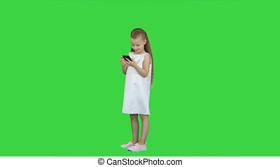 Cute little girl smiling and uses a mobile phone on a Green Screen, Chroma Key