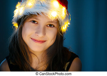 Cute little girl smiling in cristmas hat with fairy lights.