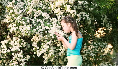 Cute little girl sniffing flowers and playing in the park in...