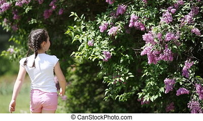 Cute little girl sniffing violet flowers in the park in sunshine summer day.