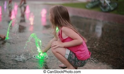 Cute little girl squatting and playing with colored water jets at the fountain in hot summer day.