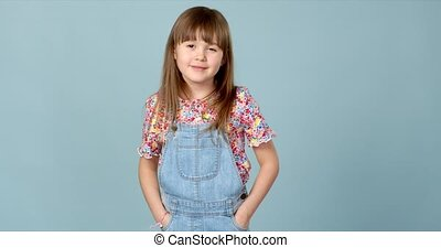 Cute little girl standing in dungarees jeans with hands in ...