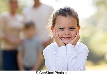 little girl standing in front of family