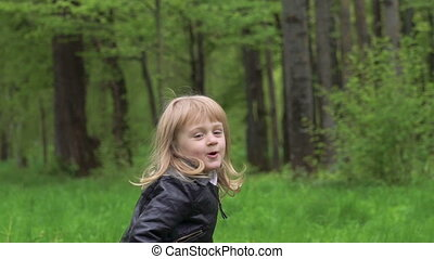 Cute little girl standing, walking on a camera and smiling in a park. Slowly