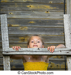little girl stands on a wooden