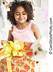 Cute little girl staring at the birthday gift