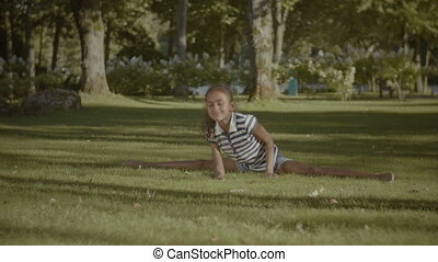Cute little girl stretching legs, doing the splits -...