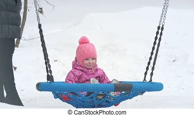 Cute little girl swinging on a swing on the playground in...