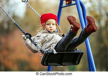 Cute little girl swinging on seesaw on children payground