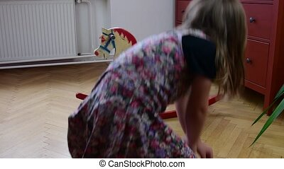 Cute little girl swings on the rocking horse. Smalll girl...