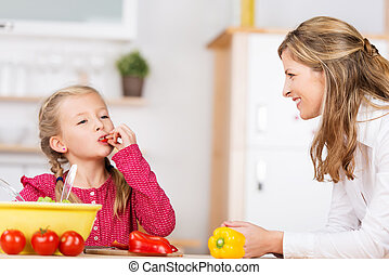 Cute little girl tasting the vegetables