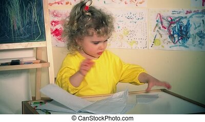 Cute little girl tearing paper book. Bored child. Static...
