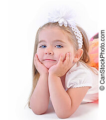 A young little girl is laying down with her hands to her face thinking. She is wearing a nice outfit on an isolated white background.