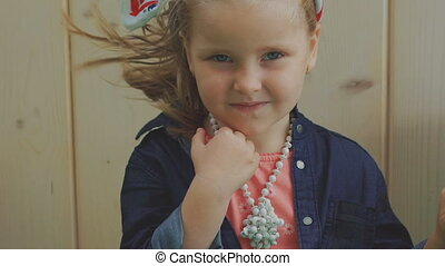 Cute little girl touches her necklace and blows air kiss at camera. Slowly