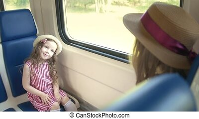 Cute little girl traveling in empty train with her mom - sends an air kiss