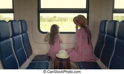 Cute little girl traveling in the train with her mom - looking at window