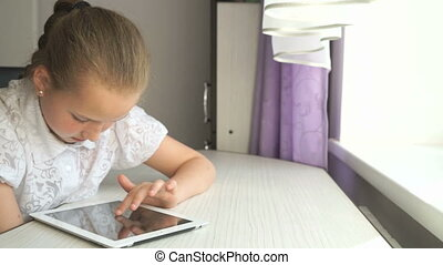 Cute little girl uses a digital tablet computer