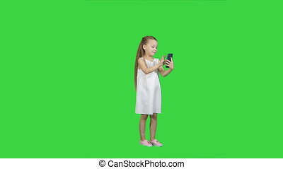 Cute little girl uses a smartphone and laugh on a Green Screen, Chroma Key