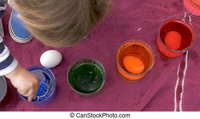 Cute little girl using her hands to grab an easter egg out of blue dye