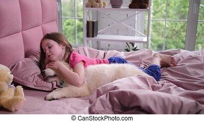 Cute little girl waking up sleepy puppy in bedroom - Sweet...