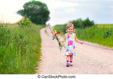 Cute little girl walking on the road with bouquet of flowers