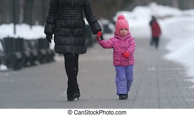 Cute little girl walking with her mother on winter street