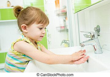 Cute little girl washing hands in bathroom