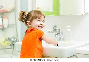 Cute little girl washing in bathroom