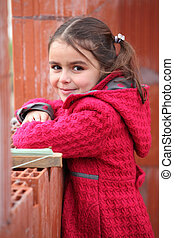 Cute little girl wearing a red coat