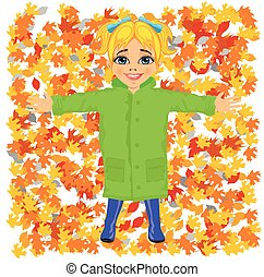 Cute little girl wearing green raincoat lying on colorful autumn leaves in park