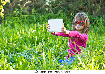 Cute little girl while taking a selfie at tablet PC in the park.