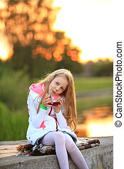 cute little girl with a Cup of tea sitting on a bench in the coo