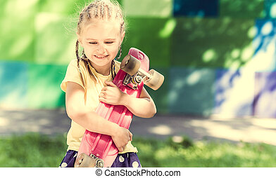 cute little girl with a skateboard on her shoulder