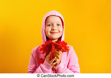 Cute little girl with an armful of autumn maple leaves on a yellow background