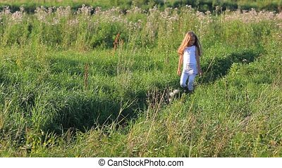 Cute little girl with blond hair picking flowers on green field way