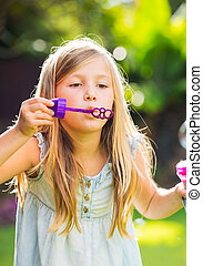 Cute little girl with blowing soap bubbles