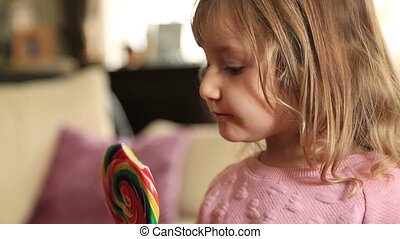 Cute little girl with candy watching tv