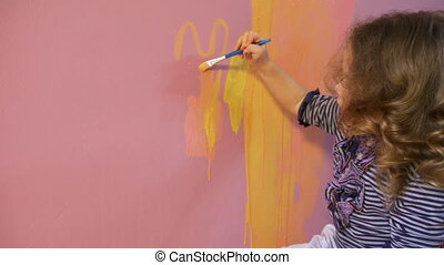 Cute little girl with curly blond hair draws on the wall
