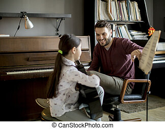 Cute little girl with guitar teacher in the room