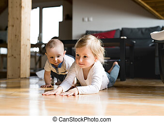 Cute little girl with her baby brother lying on the floor.