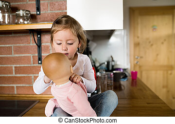 Cute little girl with her doll sitting on kitchen countertop